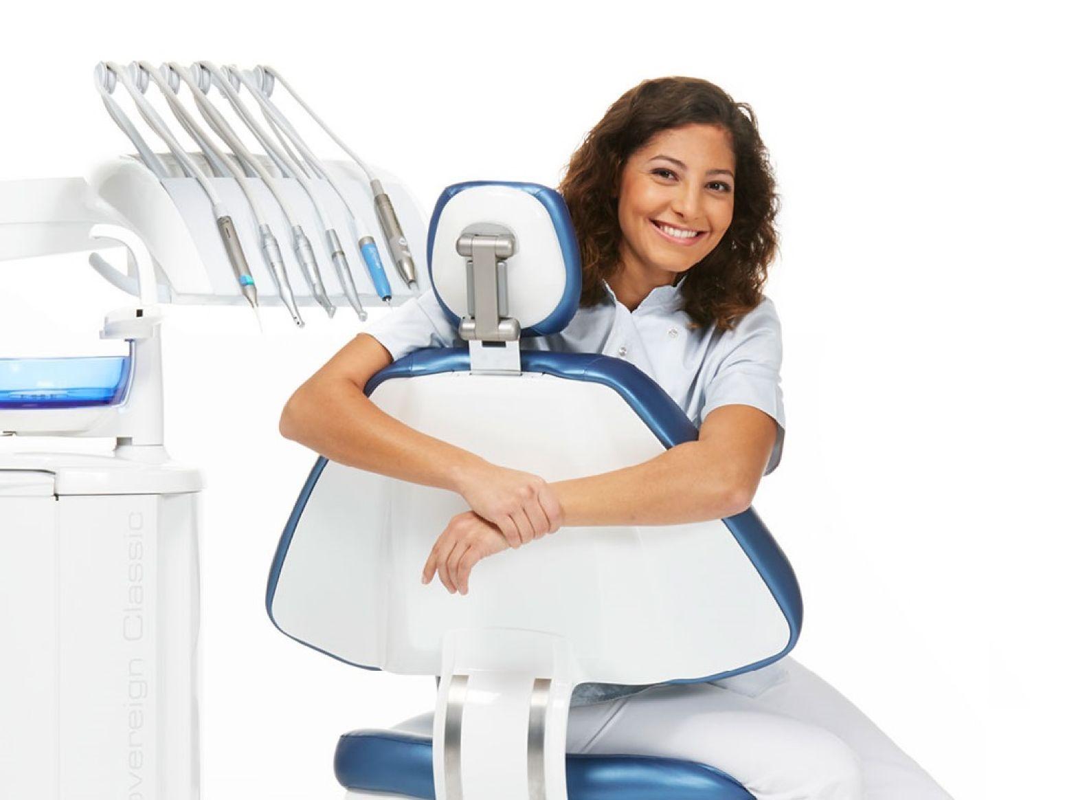 En glad kvinde sidder med armene omkring patientstolen på en tandlægeunit